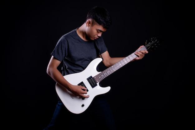 Giovane uomo in maglietta scura con chitarra elettrica