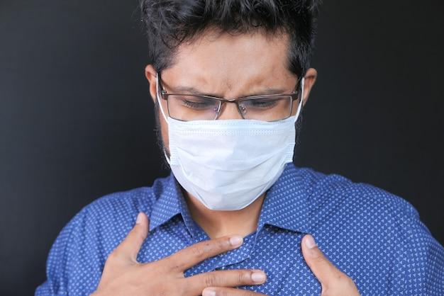 Giovane uomo in maschera protettiva che soffre di allergia influenzale, primi piani