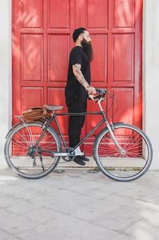 Giovane uomo in piedi con la sua bicicletta in cerca di qualcuno