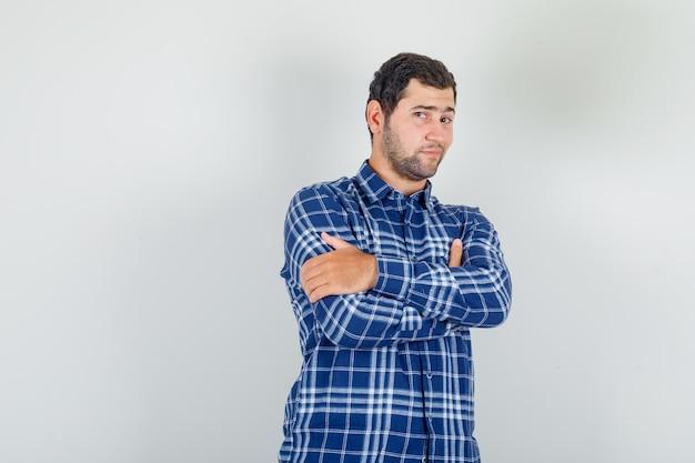Giovane uomo in piedi con le braccia incrociate in camicia a quadri e guardando fiducioso.