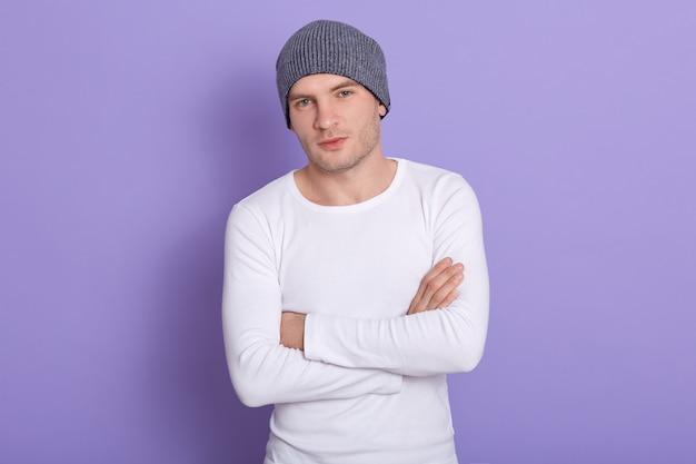 Giovane uomo in piedi con le mani giunte indossando camicia casual bianca e cappuccio grigio. copia spazio per testo pubblicitario o promozionale.