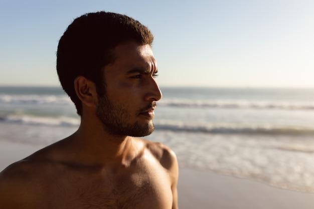 Giovane uomo in piedi sulla spiaggia