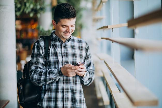 Giovane uomo in un caffè in piedi byy la finestra e parlare al telefono