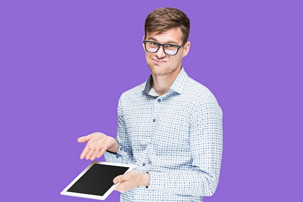 Giovane uomo in una camicia che lavora al computer portatile sul viola