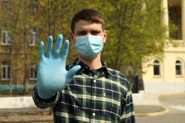 Giovane uomo in una maschera protettiva e guanti nel parco