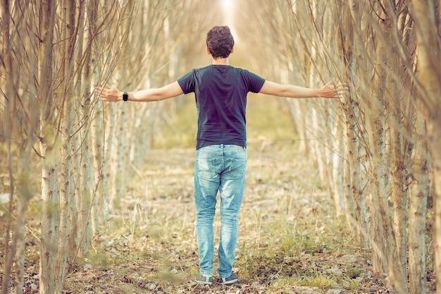 Giovane uomo in una passeggiata attraverso la natura, pensieri equilibrati e relax