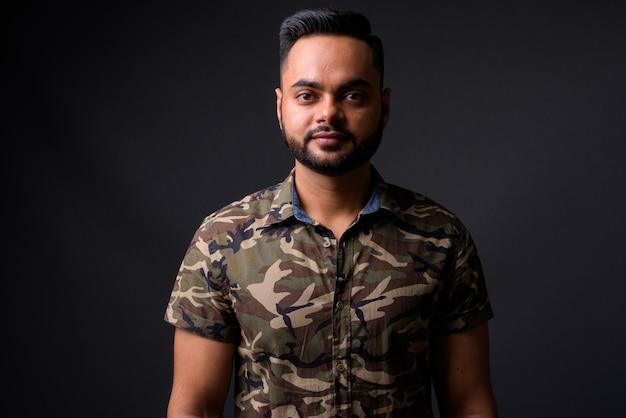 Giovane uomo indiano barbuto contro il grigio