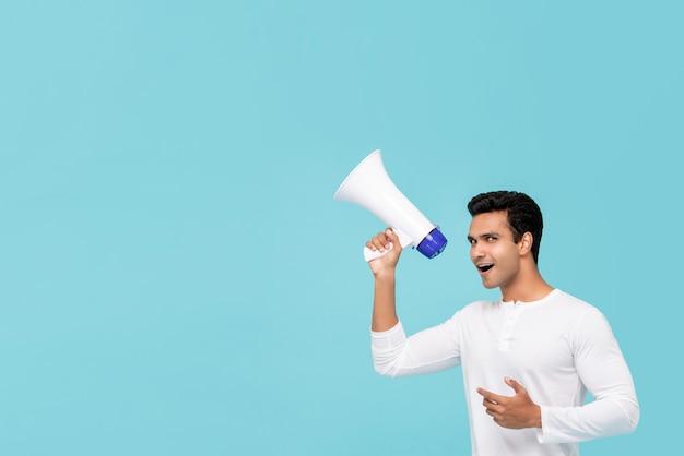 Giovane uomo indiano bello che parla sul megafono