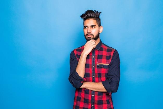 Giovane uomo indiano che indossa casuale che controlla spazio blu isolato