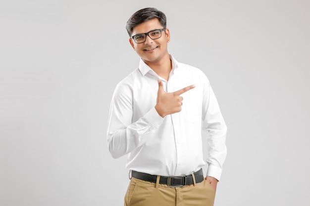 Giovane uomo indiano che mostra direzione con la mano