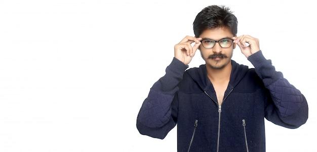 Giovane uomo indiano che tiene gli occhiali da vista