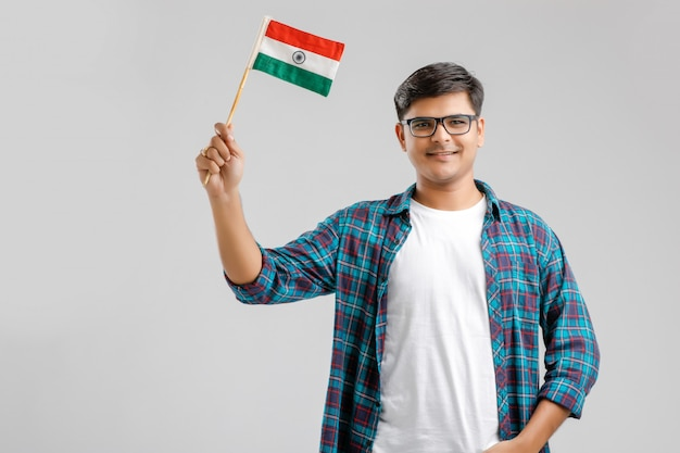 Giovane uomo indiano che tiene in mano bandiera indiana