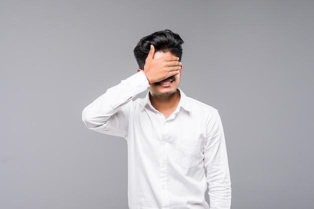 Giovane uomo indiano diritto che copre i suoi occhi di sue mani, isolate su una parete bianca.