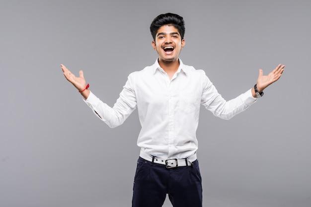 Giovane uomo indiano felice che celebra vittoria sopra la parete grigia
