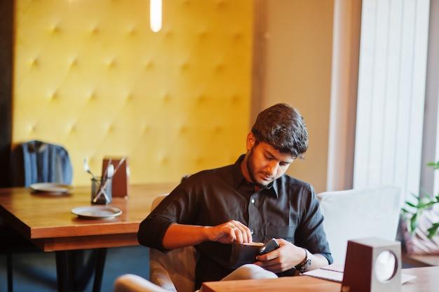 Giovane uomo indiano sicuro in camicia nera che si siede al caffè e che esamina il suo portafoglio.