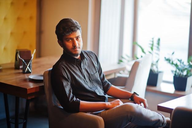 Giovane uomo indiano sicuro in camicia nera che si siede al caffè.