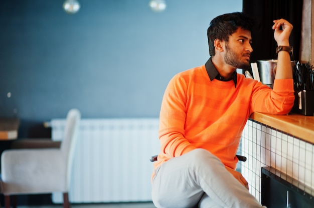 Giovane uomo indiano sicuro nel contatore di seduta della barra di maglione arancio al caffè.