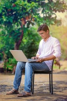 Giovane uomo indiano usando il portatile, lavorando sul portatile