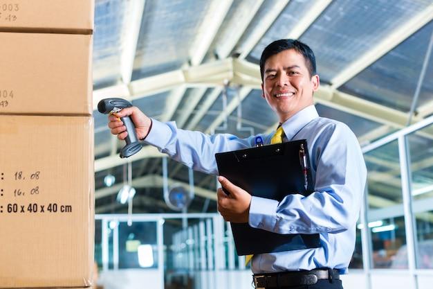 Giovane uomo indonesiano in magazzino con scanner