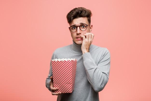 Giovane uomo intellettuale che tiene un dito del popcorn attraversando le dita per avere fortuna