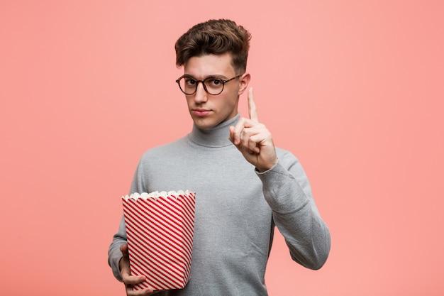 Giovane uomo intellettuale che tiene un secchio di popcorn che mostra il numero due con le dita.