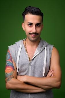 Giovane uomo iraniano bello con i baffi sul verde