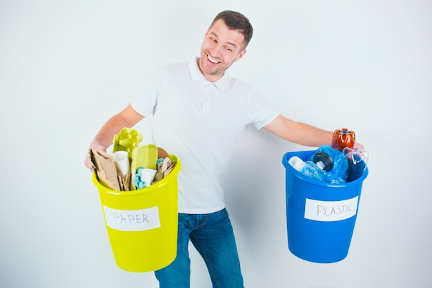 Giovane uomo isolato su un muro bianco. guy detiene pesanti secchi colorati con plastica differenziata e rifiuti di carta. abbi cura dell'ambiente. preparazione dei materiali per il riciclaggio.