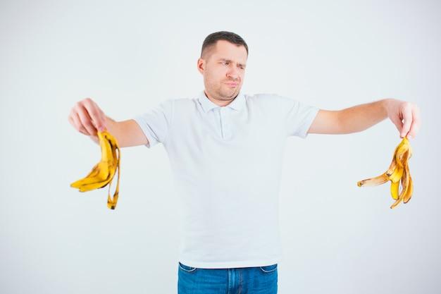 Giovane uomo isolato su un muro bianco. il ragazzo infelice medio tiene la pelle di banana tra le mani. vuoi buttarlo via. rifiuto organico.