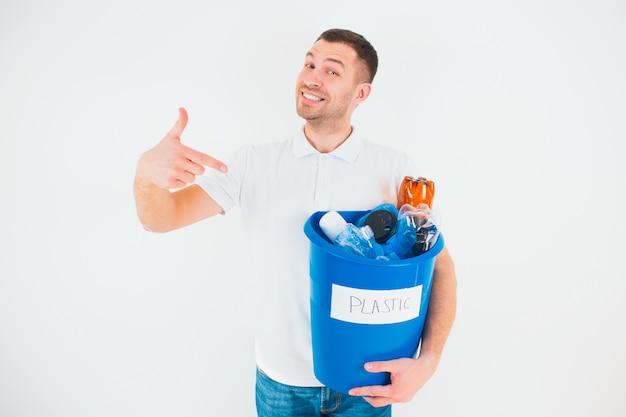 Giovane uomo isolato su un muro bianco. punto felice felice del tipo al secchio blu con le bottiglie di plastica curve dentro. tempo di riciclaggio. stile di vita senza sprechi.
