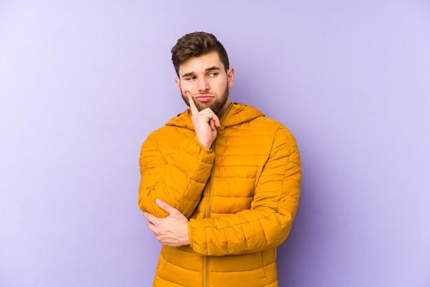 Giovane uomo isolato sulla parete viola contemplando, pianificando una strategia, pensando al modo di fare impresa.
