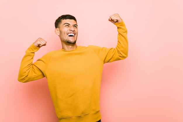 Giovane uomo ispanico che alza pugno dopo una vittoria, concetto del vincitore.