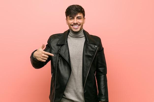Giovane uomo ispanico che indossa una persona giacca di pelle che punta a mano verso uno spazio di copia camicia, orgoglioso e fiducioso