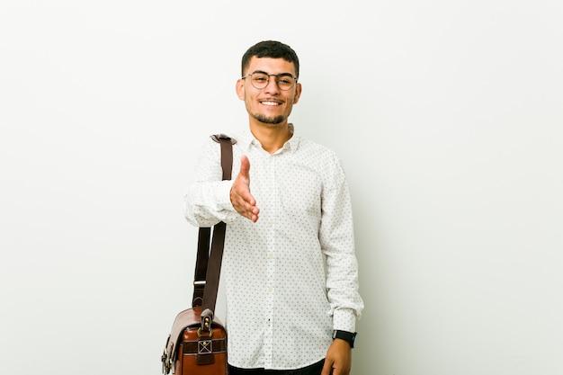 Giovane uomo ispanico di affari casuali che allunga la mano nel gesto di saluto.
