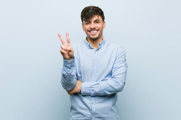 Giovane uomo ispanico di affari che mostra numero due con le dita.