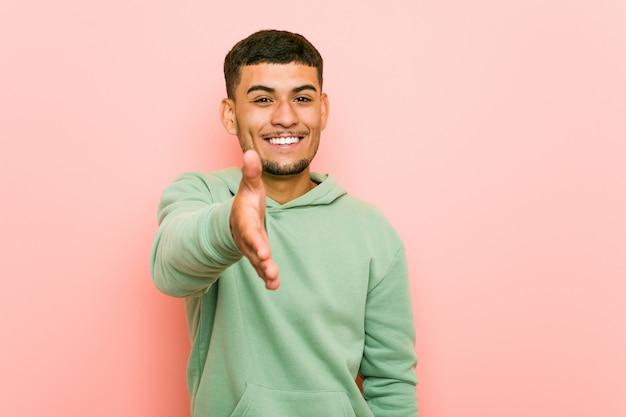 Giovane uomo ispanico di sport che allunga mano alla macchina fotografica nel gesto di saluto