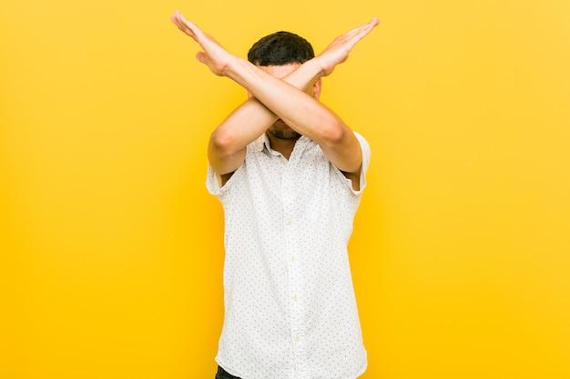 Giovane uomo ispanico tenendo due braccia incrociate, rifiuto.