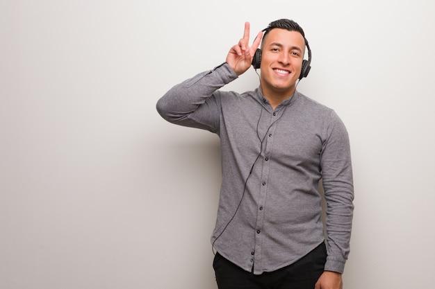 Giovane uomo latino ascoltando musica divertente e felice facendo un gesto di vittoria