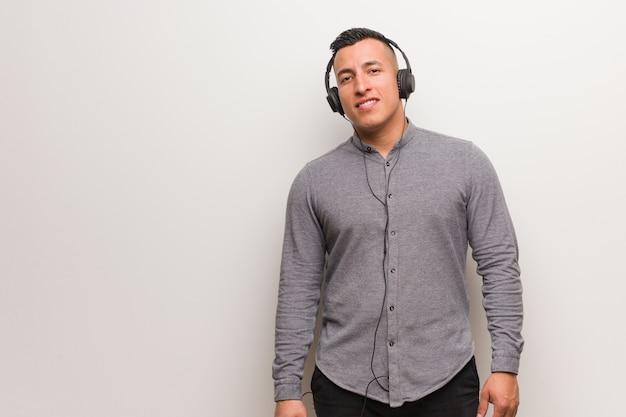 Giovane uomo latino che ascolta la musica allegra con un grande sorriso