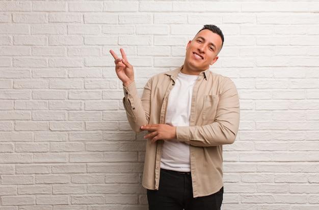 Giovane uomo latino che fa un gesto di vittoria