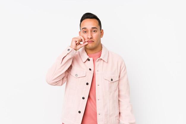 Giovane uomo latino che posa con le dita sulle labbra mantenendo un segreto.