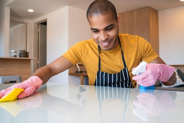 Giovane uomo latino che pulisce a casa.