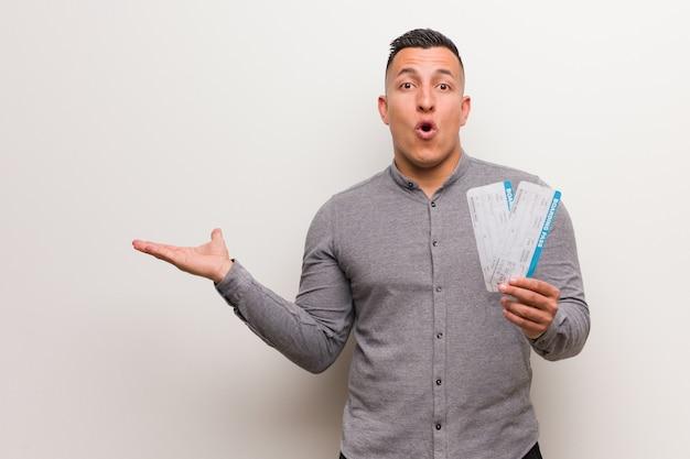 Giovane uomo latino che tiene i biglietti di aria che tengono qualcosa sulla mano di palma