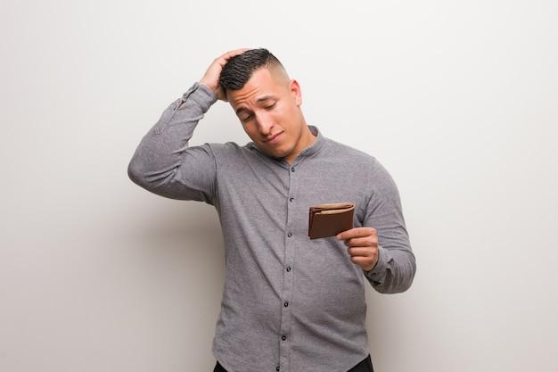 Giovane uomo latino che tiene un portafoglio preoccupato e sopraffatto