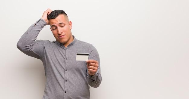 Giovane uomo latino che tiene una carta di credito preoccupata e sopraffatta