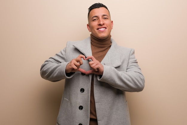 Giovane uomo latino di affari che fa una forma del cuore con le mani