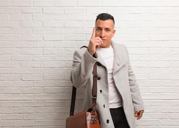 Giovane uomo latino di affari che mostra numero uno