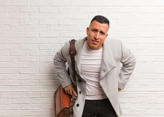 Giovane uomo latino di affari che rimprovera qualcuno molto arrabbiato