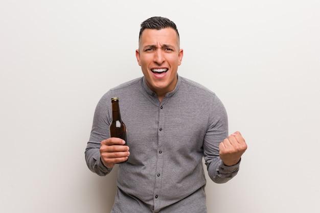 Giovane uomo latino in possesso di una birra sorpreso e scioccato