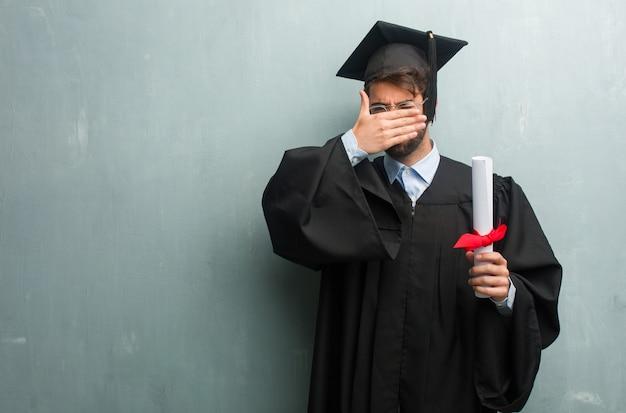 Giovane uomo laureato contro un muro grunge con uno spazio di copia guardando attraverso una lacuna
