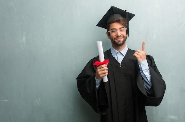 Giovane uomo laureato contro un muro grunge con uno spazio di copia mostrando numero uno, simbolo del conteggio